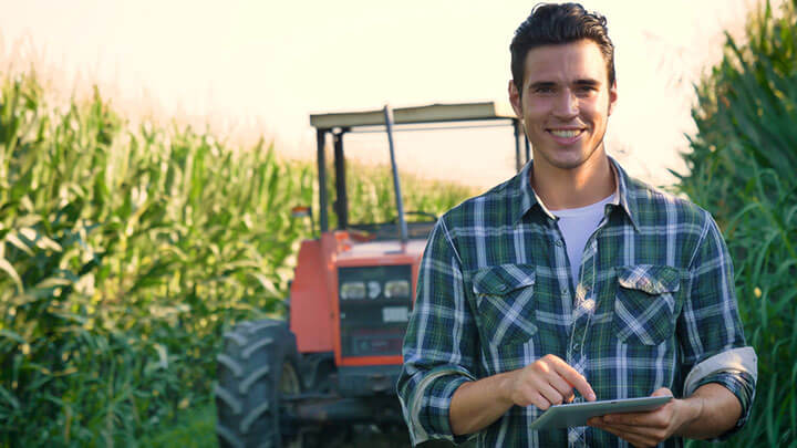young farmer working in the field with a tractor working in a tablet