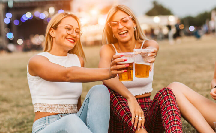 Girls sitting on the ground and cheering with beer at music festival
